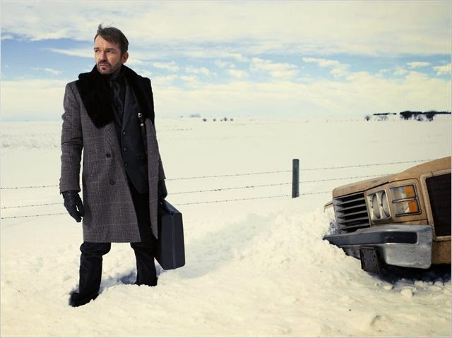 LorneMalvo, pieds dans la neige, une valisette au bras